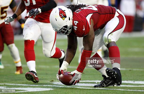 Markus Golden of the Arizona Cardinals picks up a fumble by quarterback Kurk Cousins of the Washington Redskins during the third quarter of a game at...