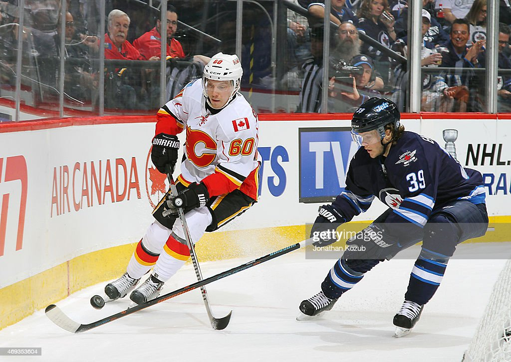 Markus Granlund #60 of the Calgary Flames battles for the puck behind the net against Toby Enstrom #39 of the Winnipeg Jets during first period action on April 11, 2015 at the MTS Centre in Winnipeg, Manitoba, Canada.