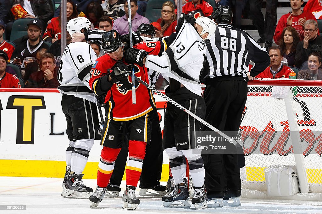Markus Granlund #60 of the Calgary Flames gets tangled up with Kyle Clifford #13 of the Los Angeles Kings at Scotiabank Saddledome on April 9, 2015 in Calgary, Alberta, Canada.
