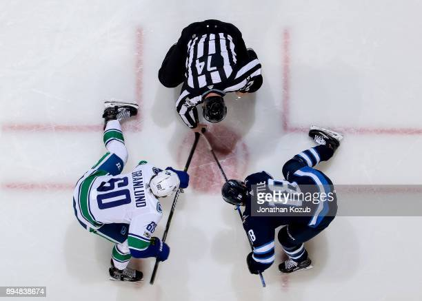 Markus Granlund of the Vancouver Canucks and Bryan Little of the Winnipeg Jets take a second period faceoff at the Bell MTS Place on December 11 2017...