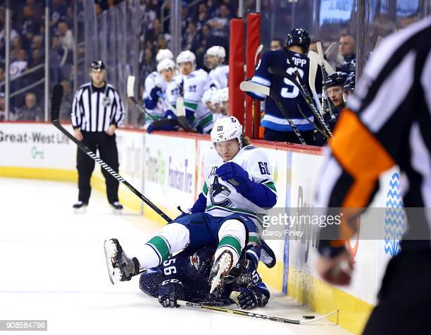 Markus Granlund of the Vancouver Canucks falls on top of Marko Dano of the Winnipeg Jets after a battle for the puck during third period action at...