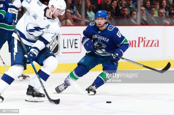 Markus Granlund of the Vancouver Canucks looks on as Victor Hedman of the Tampa Bay Lightning skates up ice with the puck during their NHL game at...