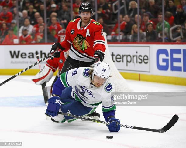 Markus Granlund of the Vancouver Canucks slips and hits the ice trying to control a puck in front of Duncan Keith of the Chicago Blackhawks at the...