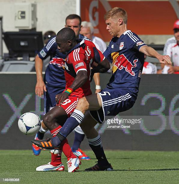 Markus Holgersson of the New York Red Bulls knocks the ball away from Dominic Oduro of the Chicago Fire during an MLS match at Toyota Park on June 17...