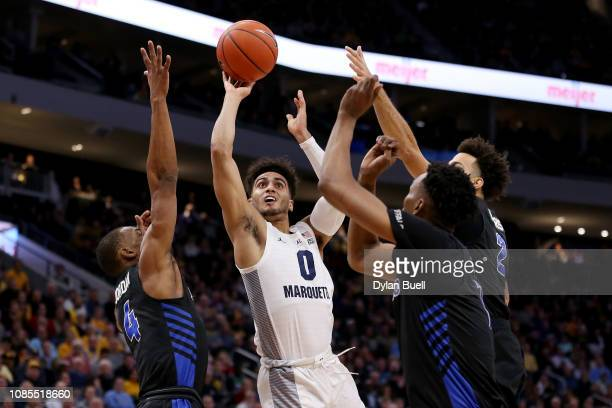 Markus Howard of the Marquette Golden Eagles attempts a shot between Davonta Jordan Jeremy Harris and Montell McRae of the Buffalo Bulls in the first...