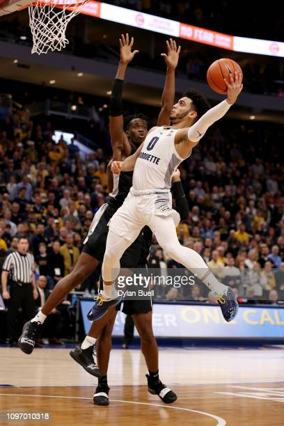 Markus Howard of the Marquette Golden Eagles attempts a shot while being guarded by Jimmy Nichols Jr #5 of the Providence Friars in the first half at...