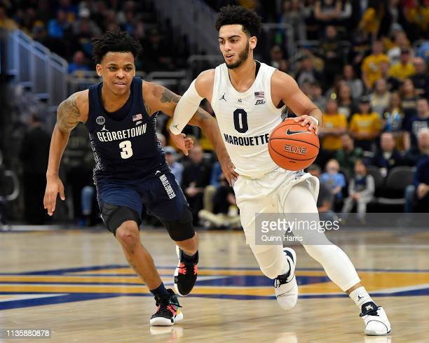 Markus Howard of the Marquette Golden Eagles drives with the ball James Akinjo of the Georgetown Hoyas at Fiserv Forum on March 09 2019 in Milwaukee...