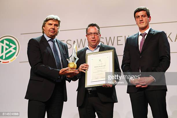 Markus Kauczinski of Karlsruher SC receives the 'Coach of the Year' award from DFB Vice President Ronny Zimmermann and Karlsruhe manager Jens Todt...