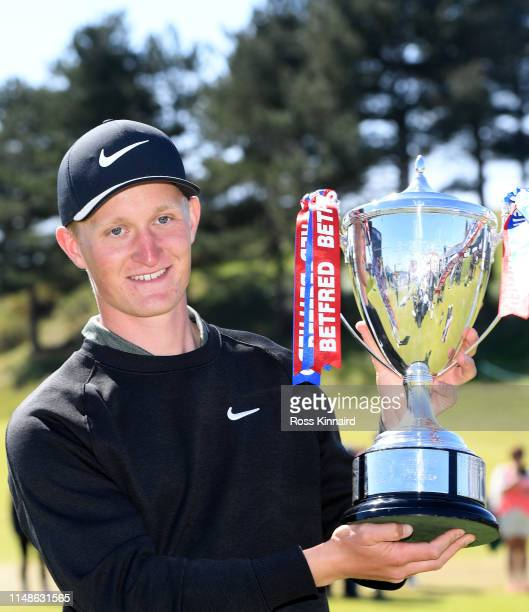 Markus Kinhult of Sweden celebrates with the trophy on the par four 18th hole during the final round of the Betfred British Masters at Hillside Golf...