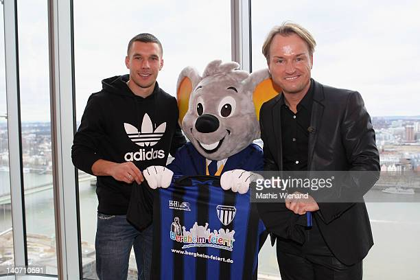 Markus Krampe and Lukas Podolski poses with the eurpapark mascot at the press conference at KölnSKY on March 5 2012 in Cologne Germany
