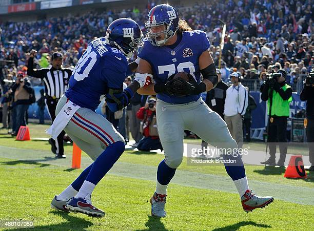 Markus Kuhn of the New York Giants is congratulated by teammate Jason PierrePaul after recoving a fumble and scoring a touchdown against the...