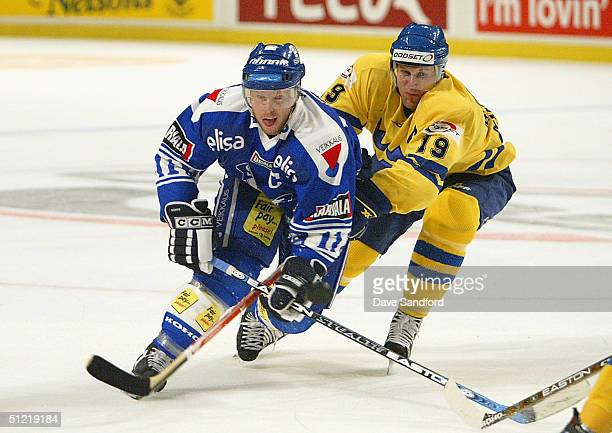 Markus Naslund of Team Sweden defends against Saku Koivu of Team Finland during an exhibition game at Globen Arena August 25, 2004 in Stockholm,...