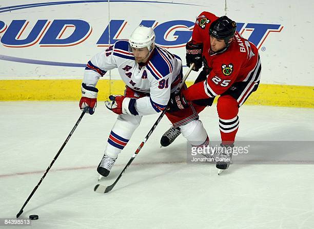 Markus Naslund of the New York Rangers protects the puck from Cameron Barker of the Chicago Blackhawks during their NHL game on January 16 2009 at...