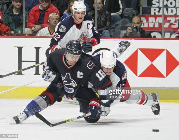 Markus Naslund of the Vancouver Canucks is checked by Rostislav Klesla of the Columbus Blue Jackets as teammate Adam Foote looks on at General Motors...