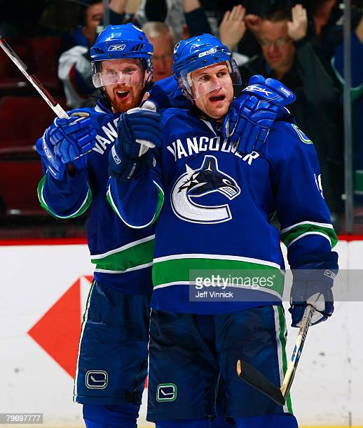 Markus Naslund of the Vancouver Canucks is congratulated by teammate Daniel Sedin after scoring during their game against the Chicago Blackhawks at...