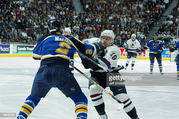 Markus Naslund of the Vancouver Canucks is punched in the face by Al MacInnis of the St Louis Blues during the first round of the 2003 Stanley Cup...