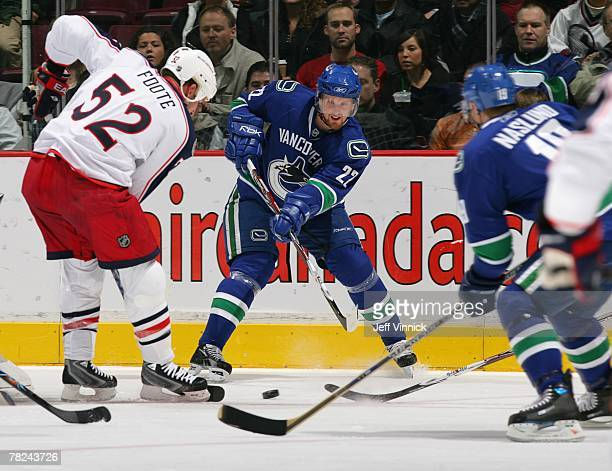 Markus Naslund of the Vancouver Canucks looks for a pass from teammate Daniel Sedin as Adam Foote of the Columbus Blue Jackets looks on during their...