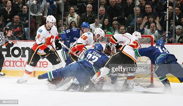 Markus Naslund of the Vancouver Canucks sneaks the puck past Miikka Kiprusoff of the Calgary Flames following Daniel Sedin of the Vancouver Canucks...