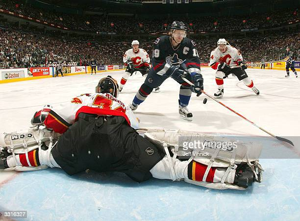 Markus Naslund of the Vancouver Canucks watches the rebound as Miikka Kiprusoff of the Calgary Flames makes a save during the first period of their...