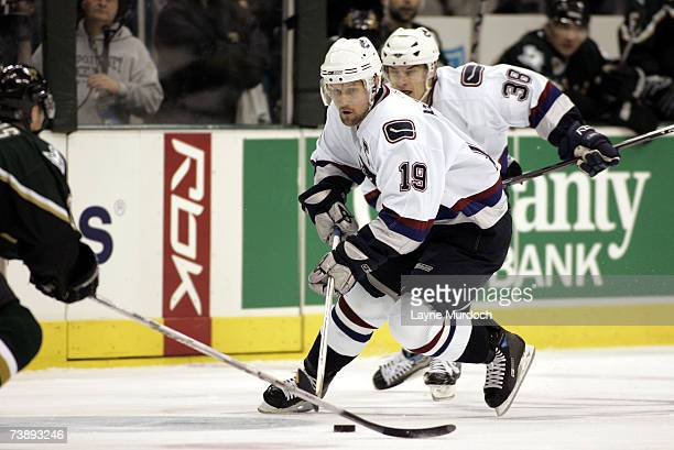 Markus Naslund of the Vancouver Canucks works the puck with teammate Jan Bulis against Stephane Robidas of the Dallas Stars during the 2nd period of...