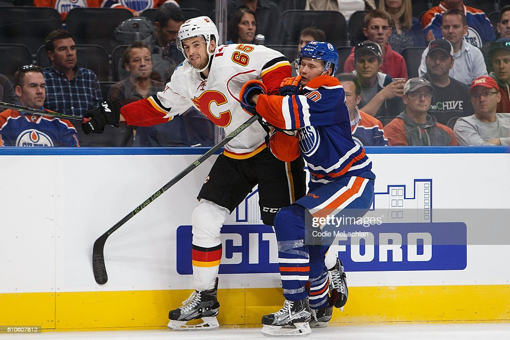 Markus Niemelainen #80 of the Edmonton Oilers skates against Jamie Devane #65 of the Calgary Flames in an NHL preseason game on September 26, 2016 at Rogers Place in Edmonton, Alberta, Canada.