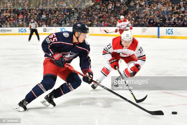Markus Nutivaara of the Columbus Blue Jackets and Brock McGinn of the Carolina Hurricanes skate after a loose puck during the first period of a game...