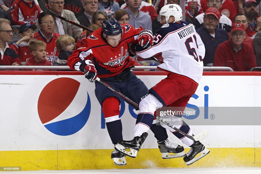 Markus Nutivaara #65 of the Columbus Blue Jackets checks Dmitry Orlov #9 of the Washington Capitals in the first period in Game One of the Eastern Conference First Round during the 2018 NHL Stanley Cup Playoffs at Capital One Arena on April 12, 2018 in Washington, DC.