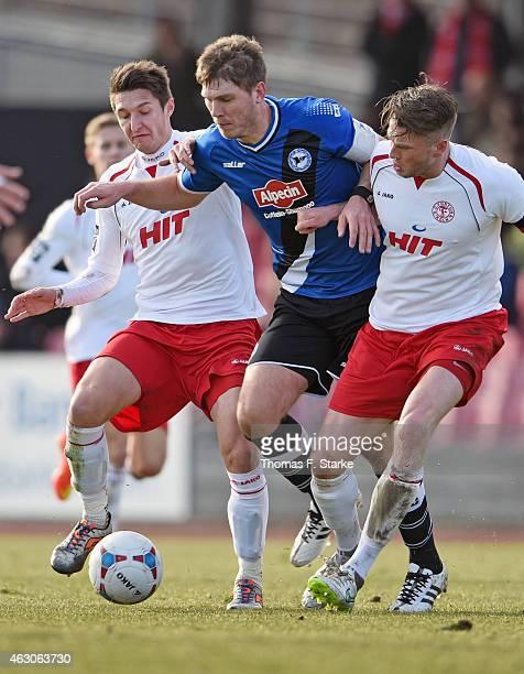 Markus Pazurek and Daniel Flottmann of Koeln tackle Fabian Klos of Bielefeld during the Third League match between between Fortuna Koeln and Arminia...