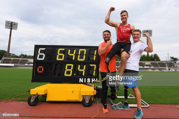 Markus Rehm of Germany is congratulated by Heinrich Popow of Germany and Daniel Jorgensen of Denmark after achieving the new world record of 8m47 in...