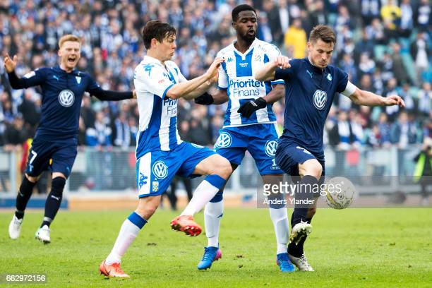 Markus Rosenberg of Malmo FF competes for the ball with Mads Albæk of IFK Goteborg and Abdul Razak of IFK Goteborg during the Allsvenskan match...