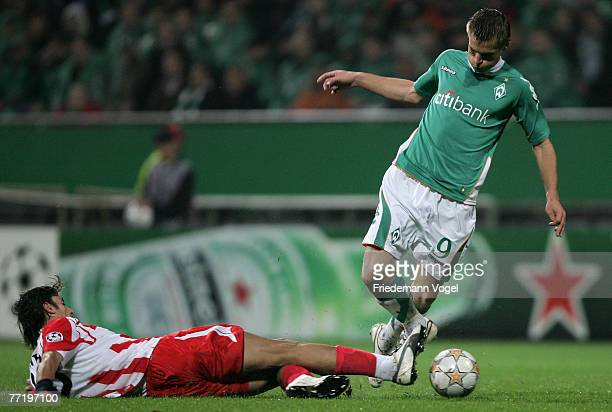 Markus Rosenberg of Werder fights for the ball with Paraskevas Antzas of Olympiakos during the UEFA Champions League Group C match between Werder...