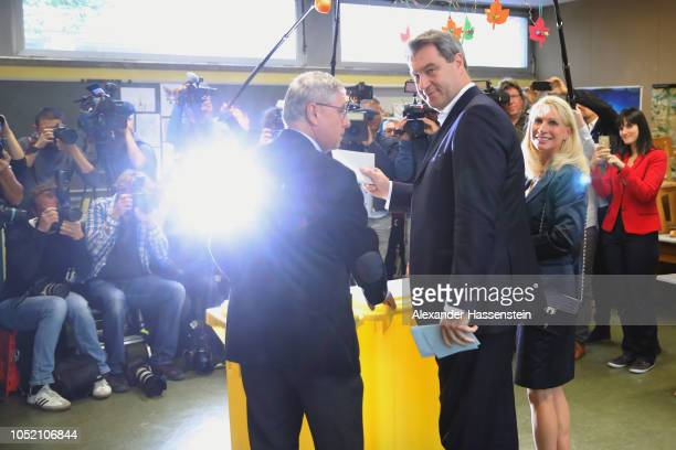 Markus Soeder, Governor of Bavaria and lead candidate of the Christian Social Union , and his wife, Karin Baumueller-Soeder, arrive to cast their...