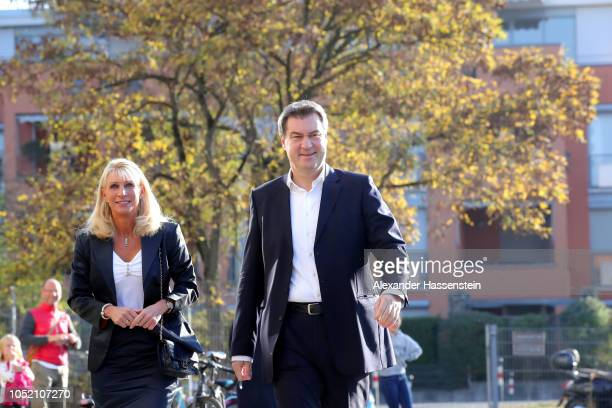 Markus Soeder Governor of Bavaria and lead candidate of the Christian Social Union and his wife Karin BaumuellerSoeder arrive to cast their ballots...