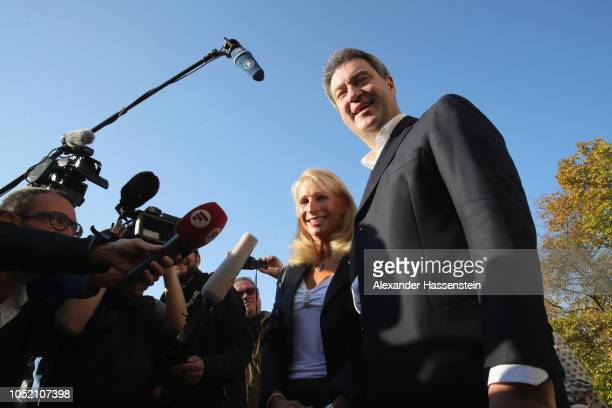 Markus Soeder Governor of Bavaria and lead candidate of the Christian Social Union and his wife Karin BaumuellerSoeder talks to the media after cast...