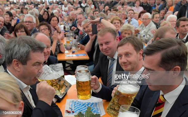 Markus Soeder left Governor of Bavaria and lead candidate of the Bavarian Social Union in upcoming Bavarian state elections drinks beer with Mike...
