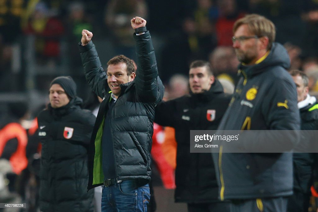 Markus Weinzierl, head coach of Augsburg celebrates victory whilst Juergen Klopp, head coach of Dortmund looks dejected after during the Bundesliga match between Borussia Dortmund and FC Augsburg at Signal Iduna Park on February 4, 2015 in Dortmund, Germany.