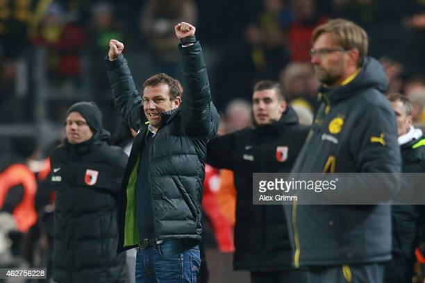 Markus Weinzierl head coach of Augsburg celebrates victory whilst Juergen Klopp head coach of Dortmund looks dejected after during the Bundesliga...