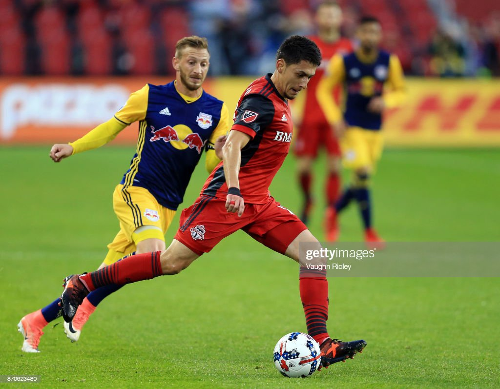 Marky Delgado #18 of Toronto FC dribbles the ball as Daniel Royer #77 of New York Red Bulls defends during the first half of the MLS Eastern Conference Semifinal, Leg 2 game at BMO Field on November 5, 2017 in Toronto, Ontario, Canada.