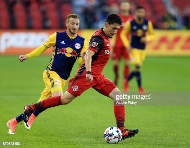 Marky Delgado of Toronto FC dribbles the ball as Daniel Royer of New York Red Bulls defends during the first half of the MLS Eastern Conference...