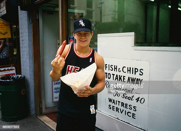 Marky Mark singer and rapper of the Funky Bunch posing with a sausage outside a fish and chip shop in London circa 1991