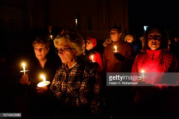 Marla Petrini far left Susan Brown second from left and Lisa Dean right join in a candlelight vigil in support of the migrant caravan outside of Park...
