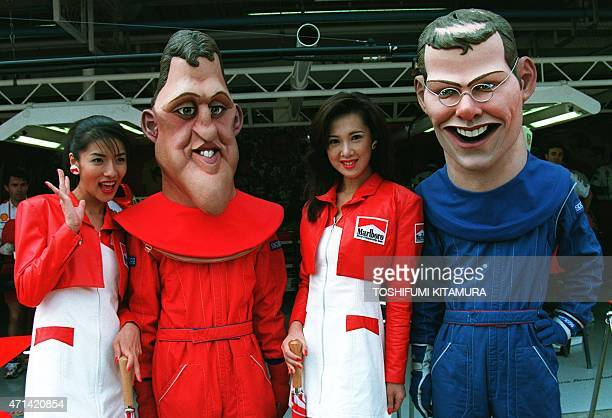 Marlboro girls Ako Shinoki and Kayo Takashiro stand beside Michael Schumacher and Jacques Villeneuve figures during the pit walk of the Japanese...