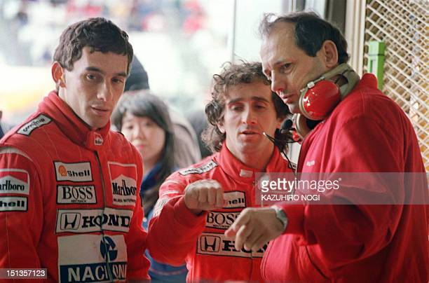 Marlboro McLaren Honda teammates Brazilian Ayrton Senna and French Alain Prost confer with a team staff member during their second qualifying...