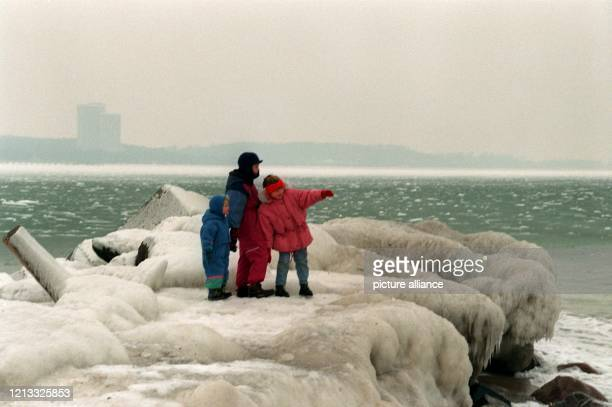 Marle Merten und die sechsjährige Beke aus Ratekau stehen am 2611996 auf einer durch Spritzwasser völlig vereisten Mole am Ostseestrand der...