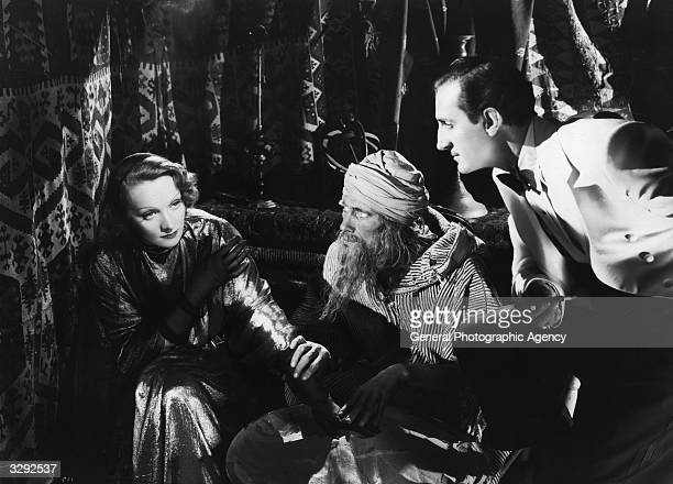 Marlene Dietrich and Basil Rathbone consult holy man John Carradine in the David O Selznick film 'The Garden Of Allah' directed by Richard Boleslawski