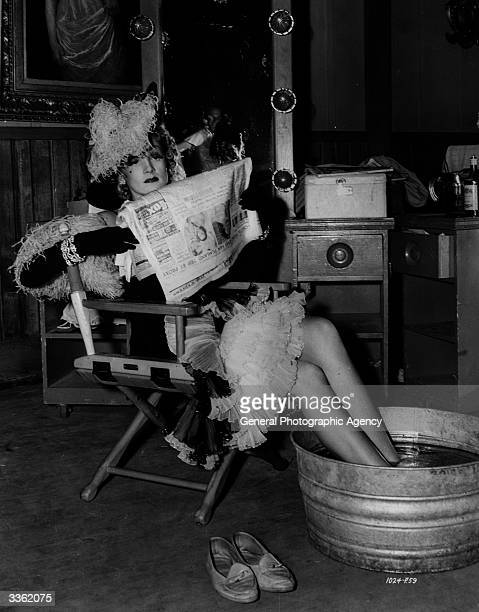 Marlene Dietrich cools her feet in a tub of iced water on the set of the classic western 'Destry Rides Again' Alternatively titled 'Justice Rides...