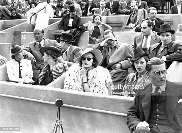 Marlene Dietrich dans sa loge assistant aux matches de tennis du championnat de France au stade Roland Garros à Paris France le 11 juin 1938
