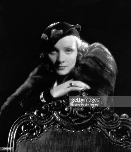 Marlene Dietrich leans against an ornately carved chair.