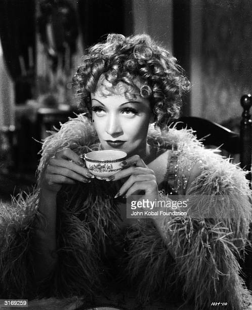 Marlene Dietrich sips a cup of tea in a scene from the film 'Destry Rides Again' directed by George Marshall