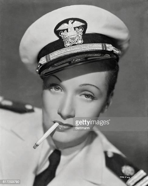 Marlene Dietrich wears the dress uniform of US Navy officer while smoking